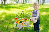 Positive boy with watering can and flowers — Stock Photo