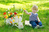 Cute kid on the grass near wheelbarrow with flowers — Stock Photo