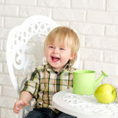 Laughing little boy at the table — Stock Photo