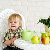 Cute kid at the table with apples — Stock Photo