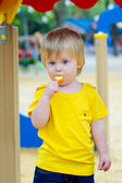 Kid eating lolly pop on the playground — Stock Photo