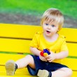 Toddler on the yellow bench — Stock Photo