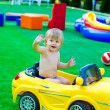 Kid in the yellow car on the playground — Stock Photo #29355383