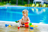 Toddler by the pool palying with toy bucket set — Stock Photo