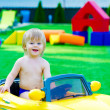 Kid in the yellow car on the playground — Stock Photo