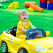 Kid in the yellow car on the playground — Stock Photo #29548189