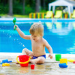 Cute kid playing with toy bucket set by the pool — Foto de Stock