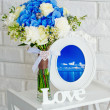 Still life with flowers, wooden letters and a vintage photo frame — Stock Photo