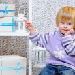 Cute little boy pointing at gift boxes  — Stock Photo