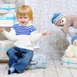 Smiling kid with gift boxes and teddy bears — Stock Photo