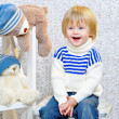Laughing kid with gift boxes and teddy bears — ストック写真