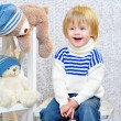 Laughing kid with gift boxes and teddy bears — Stockfoto