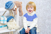 Laughing kid with gift boxes and teddy bears — Stock Photo