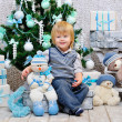 Happy kid wuth toys by the Christmas tree — Stock Photo