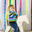 Stock Photo: Cheerful toddler riding handmade wooden horse