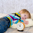 Tired toddler lying down with alarm clock in front — Stock Photo