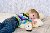 Çalar saat ile önünde yatarak yorgun yürümeye başlayan çocuk — Stok fotoğraf