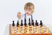 Cute little boy playing chess — Stock Photo