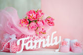 Pink tulips, baby shoes and family sign — Stock Photo