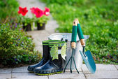 Small rain boots and garden tools — Stock Photo