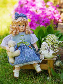 Beautiful collectible doll in the garden bloom — Stock Photo