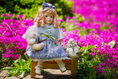 Collectable doll in the blooming garden — Stock Photo