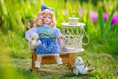 Beautiful collectible doll in the garden bloom — Stockfoto