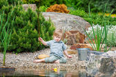 Little boy busy catching fish in the pond — Stock Photo