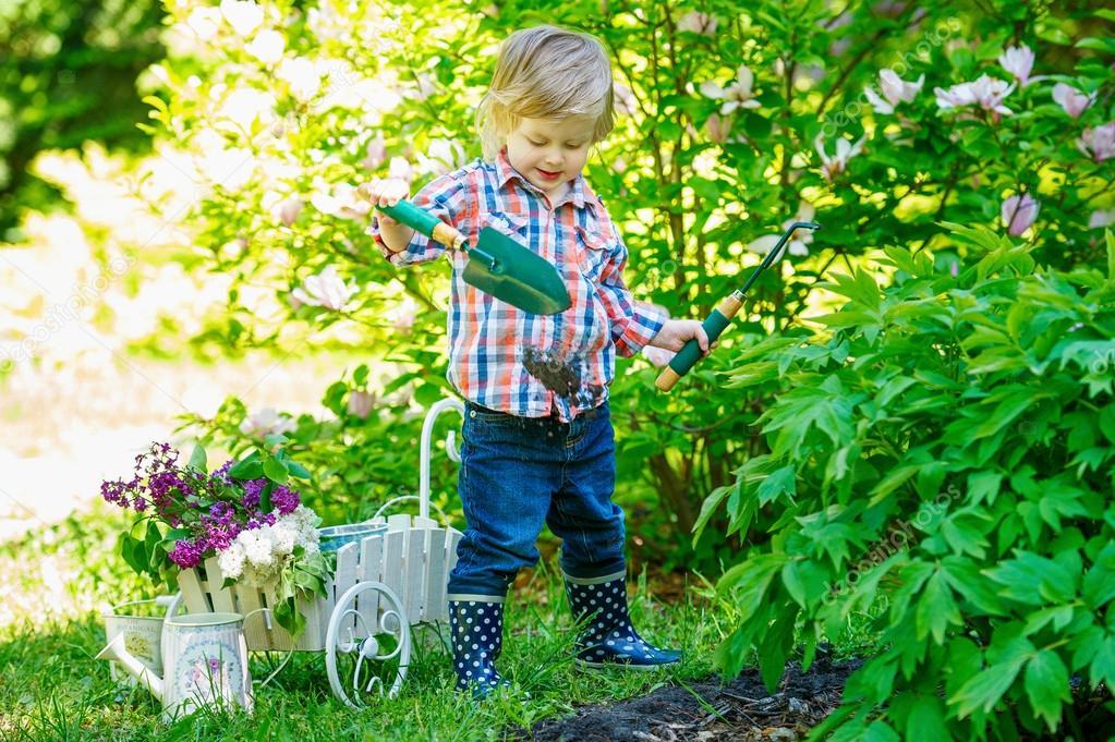 可爱的孩子在花园挖掘,用适当的餐具— 照片作者 zoiakostina