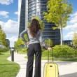 Businesswoman stands with suitcase - Stock Photo