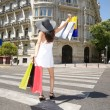 Happy walking with shopping bags on crosswalk — Stock Photo #14081459