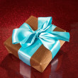 Gift on red sparkling background — Stock Photo