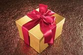 Golden gift on sparkling background — Stok fotoğraf
