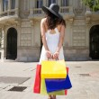White dressed woman holding shopping bags — Stock Photo