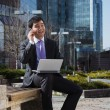 Young businessman sitting with laptop. Outdoor. — Stock Photo