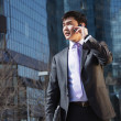 Stock Photo: Young businessman talking on mobile phone.