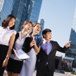Stock Photo: Happy diverse group of executives pointing over business center.