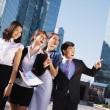 Happy diverse group of executives pointing over business center. - Stock Photo