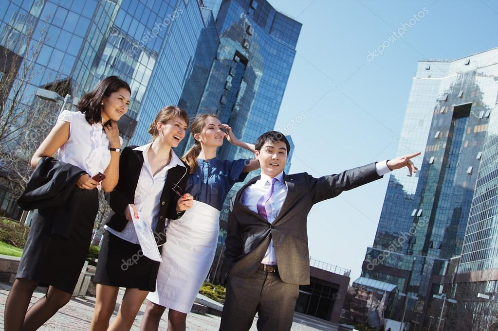Happy diverse group of executives pointing over business center. Outdoor — Stock Photo #15839207