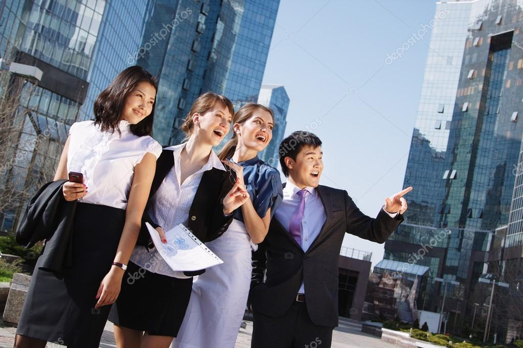 Happy diverse group of executives pointing over business center. Outdoor  Stock Photo #15839501