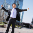 Happy asian businessman standing outside with arms outstretched — Stock Photo