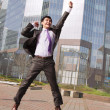 Jumping businessman over urban background - Zdjęcie stockowe