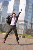 Jumping businessman over urban background — Stock fotografie