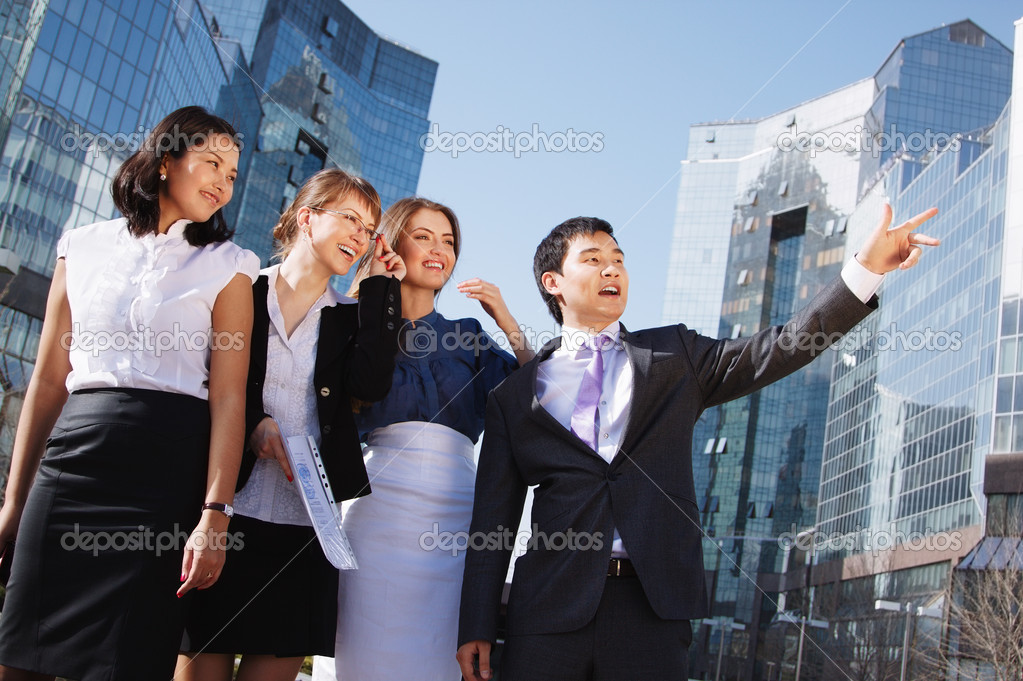Happy diverse group of executives pointing over business center. Outdoor — Stock Photo #15840263