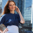 Portrait of a cute business woman over business center on back — Stock Photo