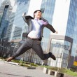 Jumping happy businessman over office buildings background — Stock fotografie