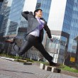 Jumping happy businessman over office buildings background — Photo