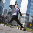 Jumping happy businessman over office buildings background - Stok fotoğraf