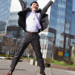 Jumping happy businessman over office buildings background - Zdjęcie stockowe