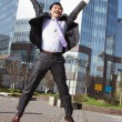 Jumping happy businessman over office buildings background — Stockfoto
